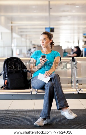 young woman waiting for her flight at airport