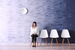 Young woman waiting for job interview in reception hall