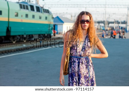 Young woman waiting train on the platform of railway station