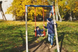 Young woman walk in green yellow fall autumn park with little cute child baby boy on nature. Mother, kid son fun rest, ride on swing. Parenthood, family day 15 of may, love, parents, children concept