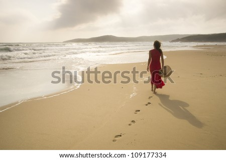 Young woman walk on an empty wild beach towards celestial beams of light falling from the sky - stock photo