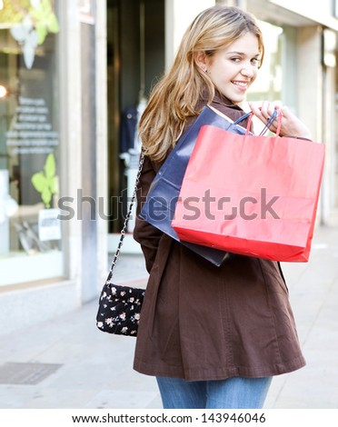 Young woman walking and shopping in the city, turning to smile at camera while carrying paper bags over her shoulder, joyful and smiling.