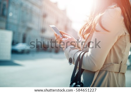 Young woman walking and using a smart phone on a city street. stock photo