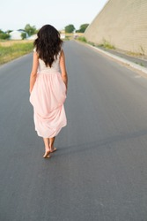 young woman walking barefoot on the road
