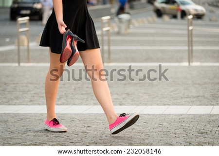 Young woman  walking down street in sneakers and high heels shoes holding in hands