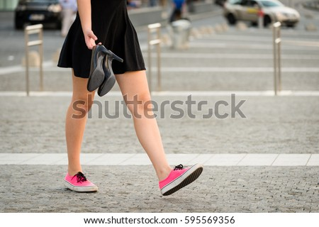 Shutterstock Young woman  walking down street in sneakers and high heels shoes holding in hands