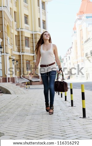 Young Woman Walking Down the Urban Street