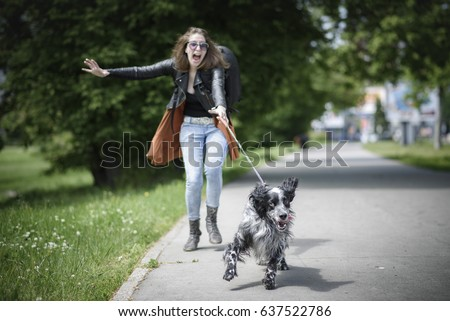 Young woman walking her dog on a street, having troubles holding him on a leash