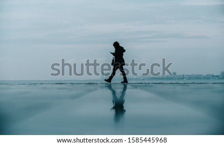 Young woman walking holding phone with reflection