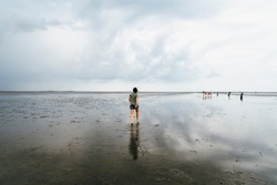 Young woman walking in a calm and tranquil beach at low tide in Wadden Sea, Germany