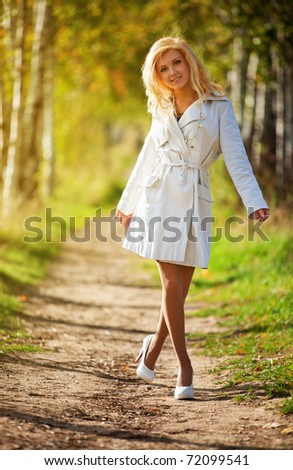 Young woman walking in autumn park.