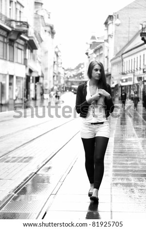 Young woman walking in the city - stock photo
