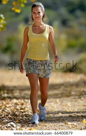 young woman walking in the park in summer