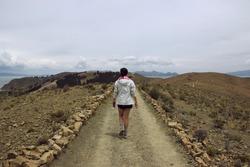 Young woman walking in the trail of Isla del Sol, Titicaca Lake, Comunidad Challa, Bolivia.