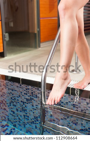Young woman walking into water basin in a wellness hotel for cooling down after sauna, only feet to be seen