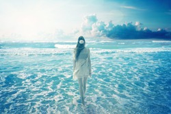 Young woman walking on a dreamy beach enjoying ocean colorful blue sky view. Landscape nature screen saver