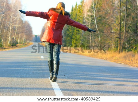 Young woman walking on asphalt road