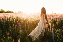 Young woman walking on flower field at sunset on background. Horizontal view with copy space