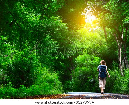 Young woman walking on green asphalt road in forest #81279994