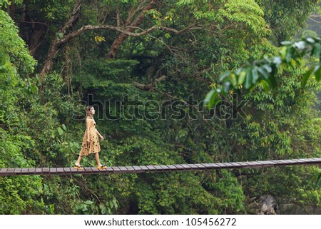 young woman walking on suspended wooden bridge in jungle, Thailand