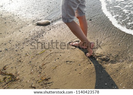 Young woman walking on the beach #1140423578