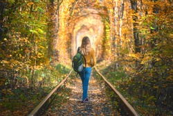 Young woman walking on the railroad in Tunnel of Love in Ukraine in autumn at sunset. Girl with backpack on railway station in tunnel of colorful trees in fall. Railroad in beautiful forest. Lifestyle