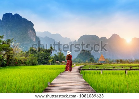 Young woman walking on wooden path with green rice field in Vang Vieng, Laos.