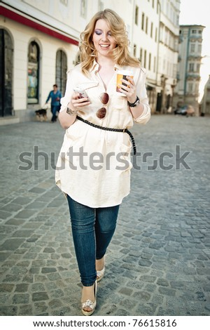 Young woman walking the street, with a coffee to go and a cell phone