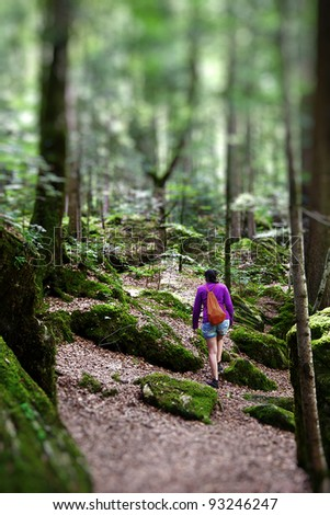 Young woman walking through a deep forest
