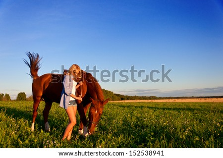 Young woman walking with a horse in the field. #152538941