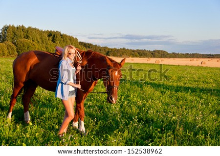 Young woman walking with a horse in the field. #152538962