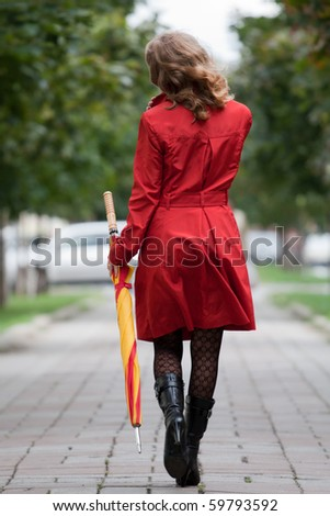 young woman walking with an umbrella
