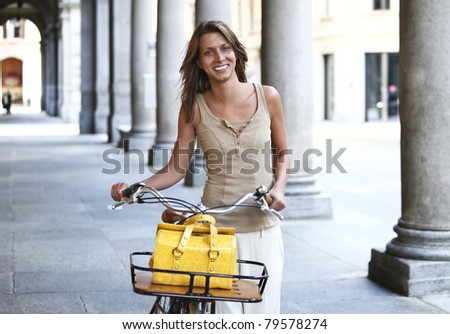 Young woman walking with her bicycle in the city - stock photo