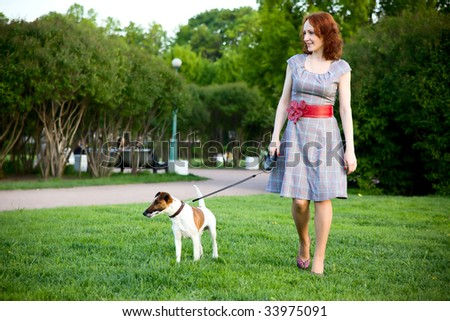 young woman walking with her dog in a park