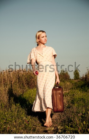 Young woman walking with suitcase in the field.