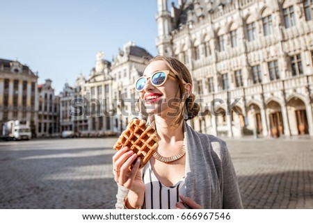 Young woman walking with waffle a traditional belgian pastry food in the center of Brussels city during the morning #666967546