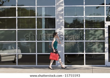 Young woman walks along building while talking on a cell phone and carrying a red bag. She is wearing a tank top. Horizontally framed photo.