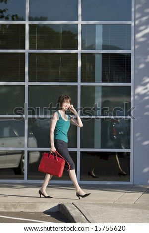 Young woman walks along building while talking on a cell phone and carrying a red bag. She is wearing a tank top. Vertically framed photo.