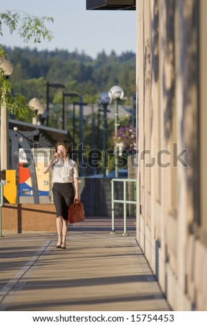 Young woman walks along building while talking on cell phone. Vertically framed photo.