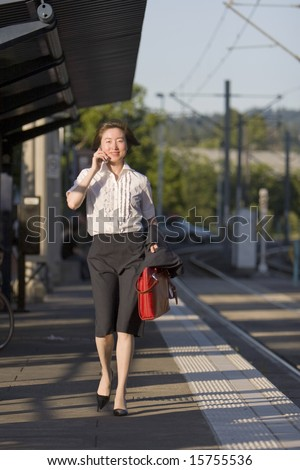 Young woman walks along tracks talking on her cell phone. She is carrying a red bag. Vertically framed photo.