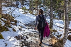 Young woman walks in the Gaube Valley frozen path surrounded by rocky slope, spruce and pine trees, near Cauterets in the Haute-Pyrénées department, France.