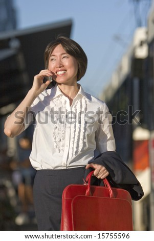 Young woman walks while talking on her cell phone. She is carrying a red bag. Vertically framed photo.