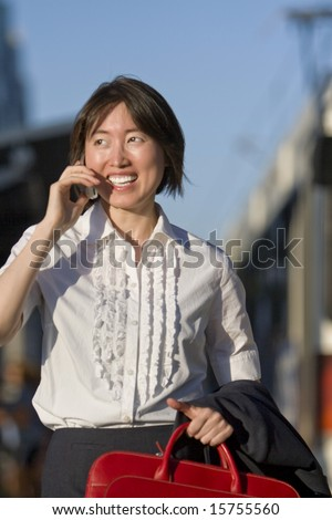 Young woman walks while talking on her cell phone. She is smiling and carrying a red bag. Vertically framed photo.