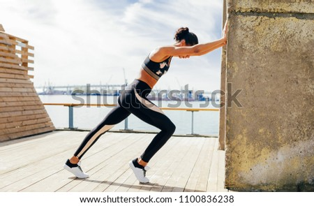 Young woman warming up and stretching near a wall