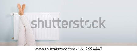 Young Woman Warming Up Legs On White Radiator ストックフォト ©