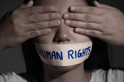Young woman was close eyes by hands and wrapping her mouth by adhesive tape with Human Rights text, Concept freedom of speech, censorship, freedom of press. International Human Rights day.