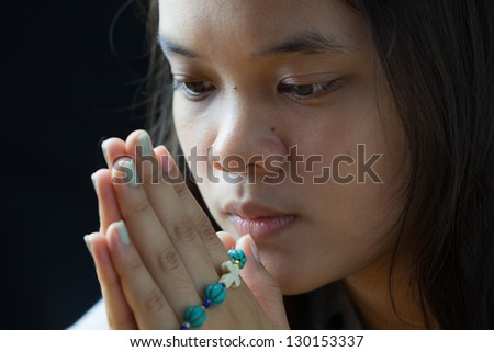Young woman was holding blue rosary in hands