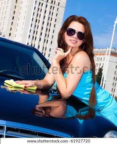 Young woman washing car. Camera angle view.