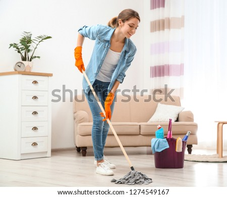 Young woman washing floor with mop in living room. Cleaning service #1274549167