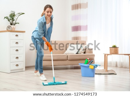 Young woman washing floor with mop in living room. Cleaning service #1274549173